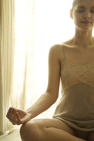 Teenage girl in front of window sitting in lotus position, eyes closed, cropped view LANG_EVOIMAGES