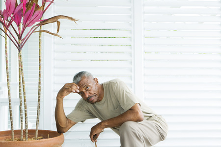 arrodillarse: Man kneeling beside potted plant, holding head, looking at camera LANG_EVOIMAGES