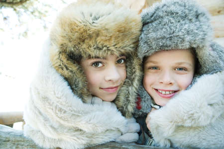 Brother and sister smiling at camera, cheek to cheek, both wearing fur caps, portrait