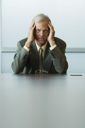 burned out: Businessman sitting with head in hands, looking at camera LANG_EVOIMAGES