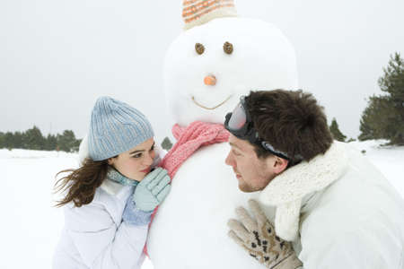 Young couple looking around snowman at each other, smiling, portrait