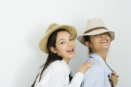 Two young female friends wearing hats and ties, smiling at camera, one placing hand on the others shoulder