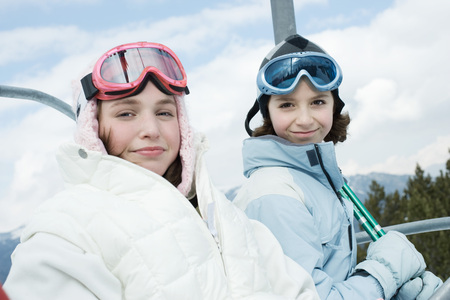 kids at the ski lift: Teenage girl and younger friend taking ski lift, portrait