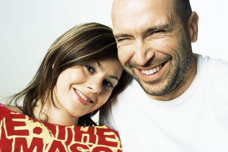 Woman leaning her head on mans shoulder, both smiling at camera