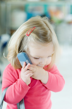 Blonde toddler girl holding cell phone to ear LANG_EVOIMAGES