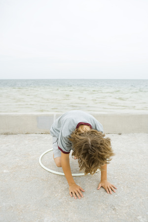game over: Boy crouching on all fours, playing with plastic hoop, head down LANG_EVOIMAGES