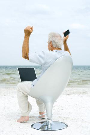Senior man using laptop and cell phone on beach, raising arms