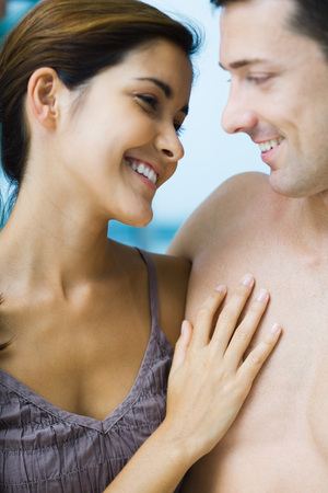 Couple smiling at each other, womans hand on mans bare chest, close-up LANG_EVOIMAGES