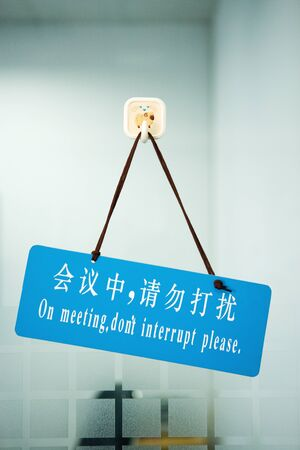 Bi-lingual sign on door stating On meeting, dont interrupt please, in Chinese script and English LANG_EVOIMAGES