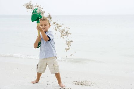 Young boy at the beach holding up shovel, throwing sand, eyes closed LANG_EVOIMAGES