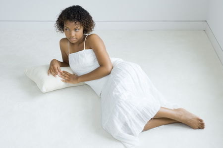 Young woman lying on cushion on the ground, looking away, full length