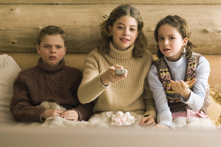 Three young siblings watching TV, teen girl changing channel while brother and sister complain
