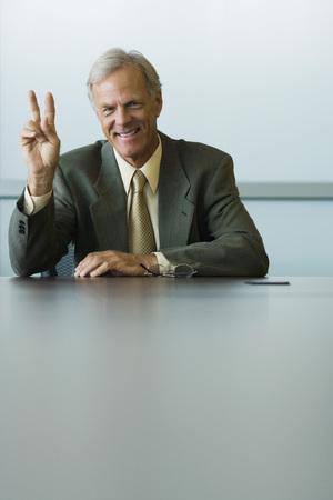 Businessman making peace sign, smiling at camera