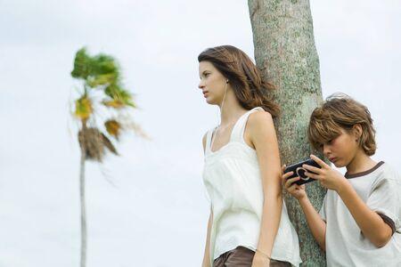 jugando videojuegos: Siblings leaning against tree trunk, boy playing handheld video game, teen girl listening to earphones
