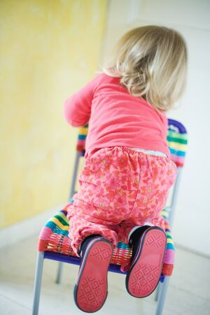 Blonde toddler girl climbing on chair, rear view LANG_EVOIMAGES