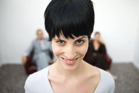 Woman smiling at camera, one eyebrow raised, close-up
