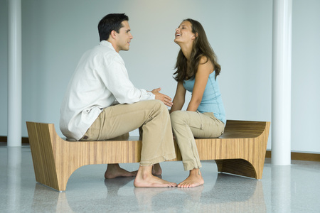 Young couple sitting face to face on bench, laughing together