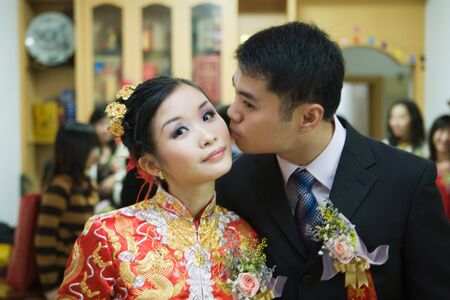 smooching: Bride dressed in traditional Chinese clothing, looking at camera as groom kisses her on the cheek