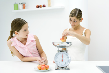 levantar peso: Mother and daughter weighing apples on scale, looking at each other
