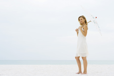 oneself: Woman standing at the beach holding parasol, looking away