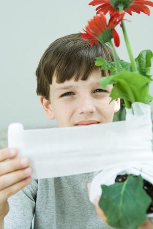 Boy wrapping gauze around gerbera daisies, looking at camera