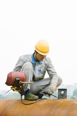 Worker crouching on metal pipe, holding welding mask, looking down LANG_EVOIMAGES