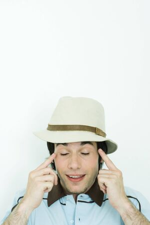 Young man wearing hat, pointing at temples, eyes closed