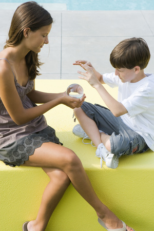 Teenage girl and younger brother sitting, looking at crystal ball together