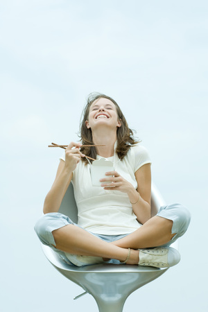 Teenage girl sitting in chair, holding chopsticks and take out food container, eyes closed