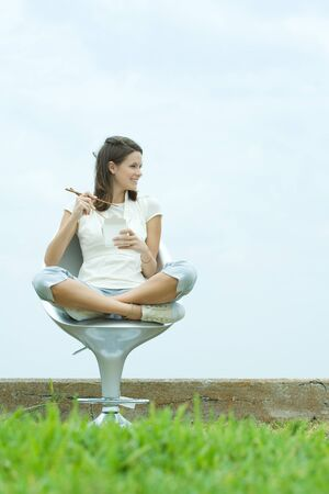 Teenage girl sitting in chair outdoors, holding chopsticks and take out food container, looking away