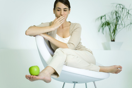 Young woman slouching in chair, balancing apple on foot, covering mouth