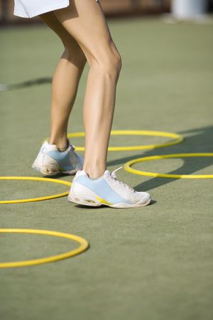 Teenage girl in tennis shoes standing beside plastic hoops, low angle view, cropped LANG_EVOIMAGES