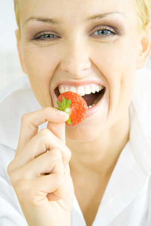 beauties: Woman biting into strawberry LANG_EVOIMAGES