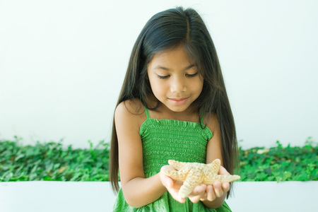 Girl holding starfish in hands LANG_EVOIMAGES