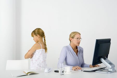 Woman sitting at table using desktop, daughter standing nearby with her back turned and arms folded