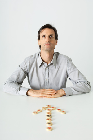 unease: Man sitting at table, Chinese game pieces in shape of arrow pointing to him