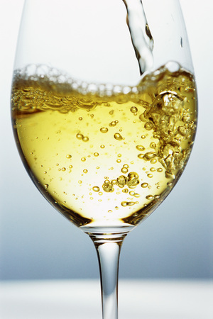 in low spirits: White wine being poured into wine glass, close-up