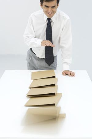 Businessman knocking over binders, smiling at camera LANG_EVOIMAGES