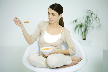 Young woman sitting in chair, holding cereal bowl, looking at spoon LANG_EVOIMAGES