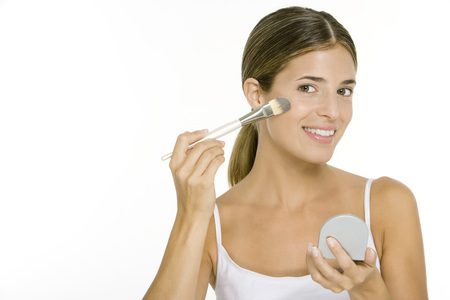 Woman applying blush, holding hand mirror, smiling at camera LANG_EVOIMAGES