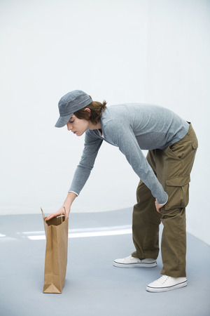 curiousness: Young man bending over, looking in paper shopping bag, side view