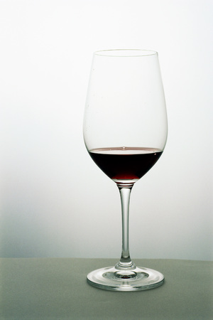 Small amount of red wine in wineglass