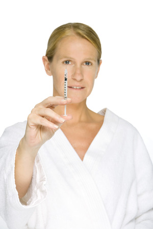 beauties: Woman in bathrobe holding up syringe, looking at camera