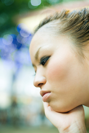 Young woman with hand under chin, profile