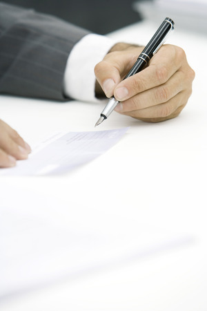 Businessman signing check, cropped view of hand