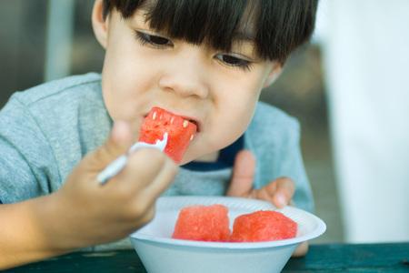 Little boy eating chunks of watermelon