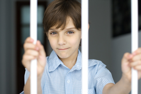 Boy behind bars, smiling at camera