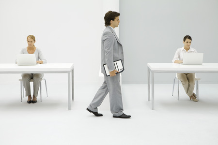 authoritative woman: Businessman walking in office, carrying document under arm, female colleagues working in background