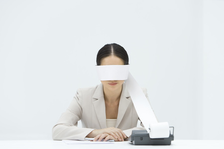Woman sitting at desk, tape from an adding machine wrapped around her eyes, arms folded LANG_EVOIMAGES