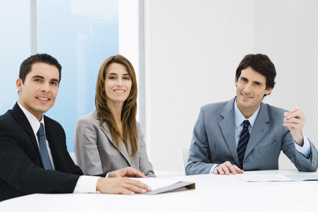 Business colleagues sitting at table, smiling at camera